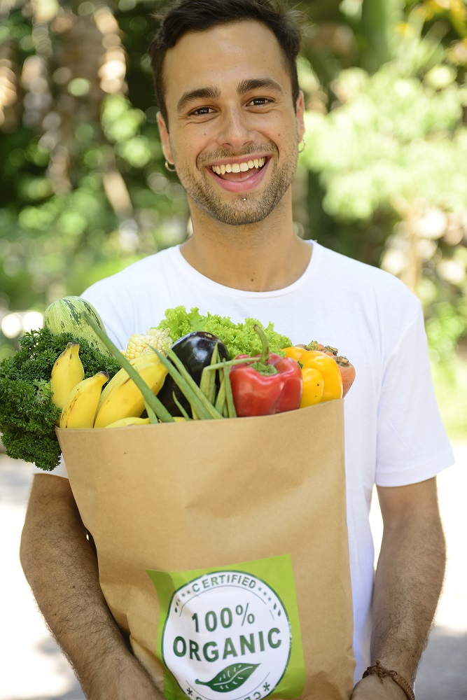 Happy man carrying a bag full of organic food.